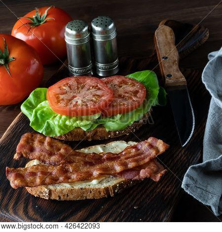 Close Up Of An Open Bacon And Tomato Sandwich Against A Dark Background.