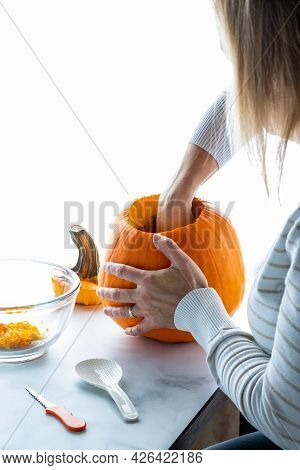 Lady Cleaning Out The Inside Of A Pumpkin Preparing It For Carving.