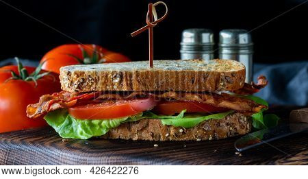 Front View Of A Bacon And Tomato Sandwich Against A Dark Background.