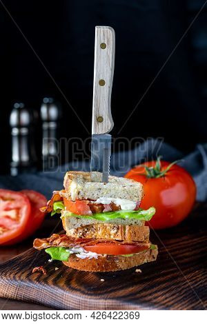 Close Up View Of A Stacked Bacon And Tomato Sandwich With A Knife Sticking Out, Against A Black Back