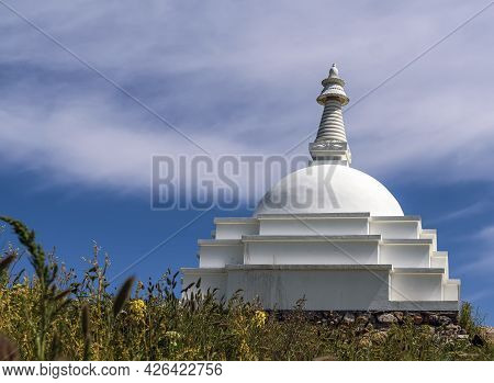 Buddhist Stupa On Top Of A Mountain Against The Clear Blue Sky.
