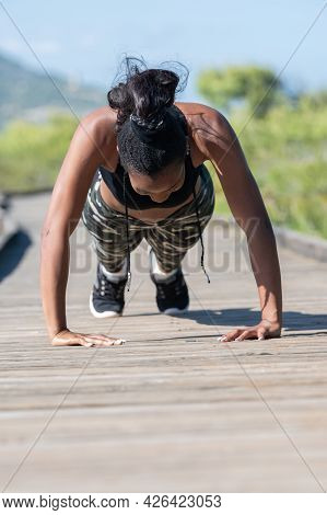 Strong Afro American Woman Doing Push Ups On A Wooden Runway: Exercise And Healthy Lifestyle Concept