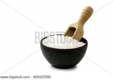 Grated Coconut, Culinary Ingredient In Rustic Earthenware Bowl With Measuring Spoon, Isolated White