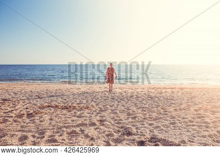 A Lonely Girl Walking Alone Towards The Sea On A Deserted Beach At Sunset With Copy Space