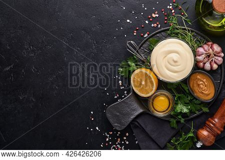 Homemade Mayonnaise Sauce And Ingredients Lemon, Eggs, Olive Oil, Spices And Herbs, Black Background