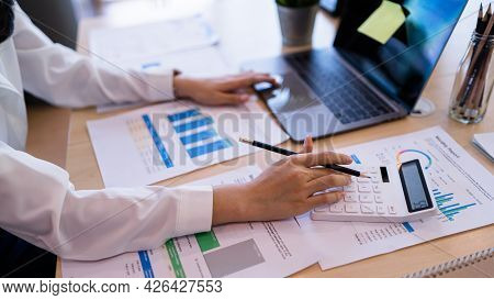 Businesswoman Accountant Using Calculator And Laptop For Calculating Finance And Accounting Analyze