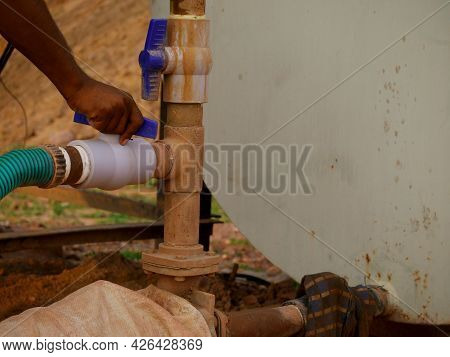 Asian Male Technician Operating Water Pipe Regulator At Construction Sight.