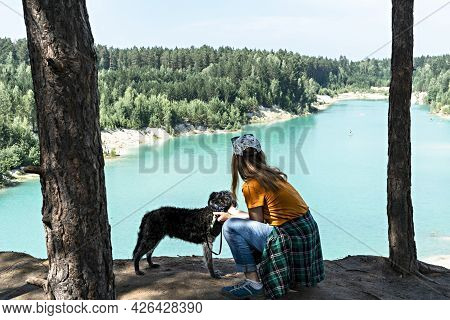 Rear View Of Young Blond Woman Traveler In Cap And Ginger T-shirt Standing On Cliff Of Blue Turquois