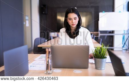 Portrait Asian Businesswoman Intends To Working With Laptop On Table At Smart Modern Office. Concept