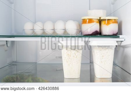 Cottage Cheese And Yoghurts With Egg Are On The Shelf In Refrigerators, Front View Close-up