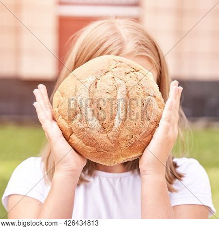 Child Holds And Bite Round Bread. Healthy Food. Carrying Big Fresh Baker Bun. Rustic Product. Enjoy