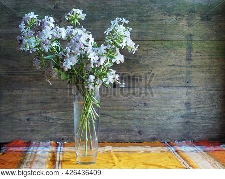 A Bouquet Of Flocs In A Vase On An Old Wooden Background. Pastoral Country Mood