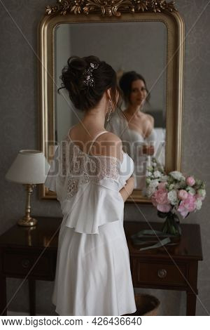 A Young Pretty Woman With Bridal Coiffure In Lace Peignoir Is Posing In Front Of The Mirror. A Beaut