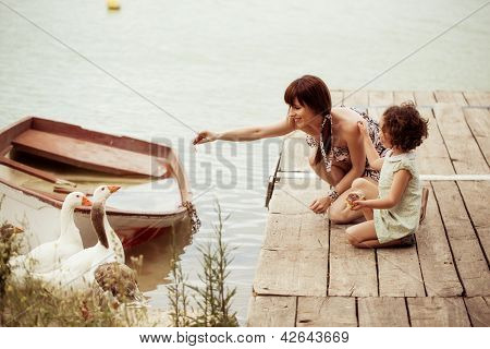 Lovely mother and daughter feeding gooses on the lake