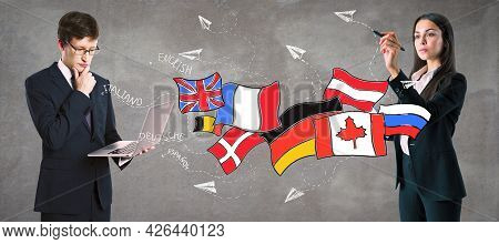 Attractive European Businessman And Woman Standing On Concrete Wall Background With Creative Flags S