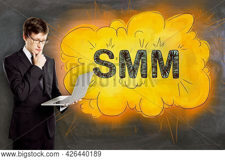Attractive Businessman With Laptop And Creative Bright Smm Cloud Sketch On Concrete Wall Background.