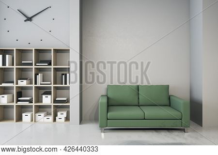 Modern Waiting Area In Office With Bookcase, Comfortable Green Couch And Mockup Place On Wall. Mock