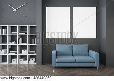 Modern Waiting Area In Office With Bookcase, Comfortable Blue Couch, Wooden Flooring And Empty Poste