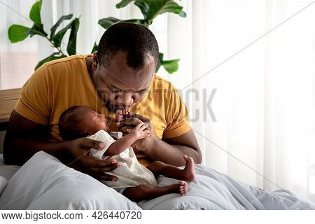 An African American Father Kissing Hand, His 12-day-old Baby Black Skin Newborn Son Lying In Bed, Wi