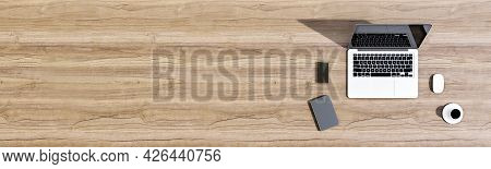 Top View Of Wooden Office Desktop With Laptop, Coffee Cup, Smartphone, Other Items And Mock Up Place