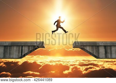 Businessman Jumping Over Concrete Gap On Beautiful Sunset Background. Success And Challenge Concept
