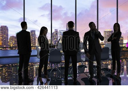 Backlit Businesspeople Standing In Panoramic Office Interior With City View. Teamwork And Success Co