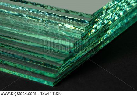 Sheets Of Factory Manufacturing Tempered Clear Float Glass Panels Cut To Size. Dark Background.