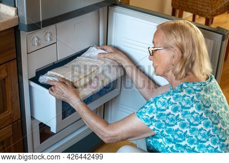 Senior Woman Putting Bed-clothes In The Fridge Freezer. How To Stay Cool In Hot Weather. Beat The He