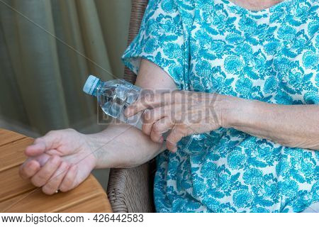 Senior Woman's Hand Holds Bottle With Cold Water On Her Elbow Bend. How To Stay Cool In Hot Weather.