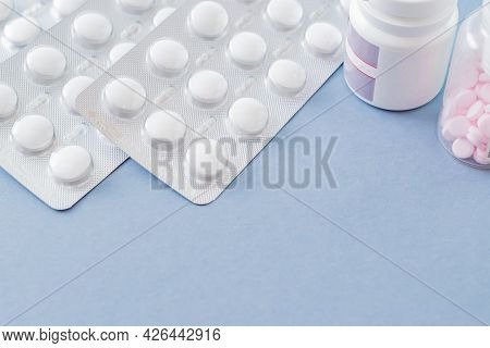 White Pills In A Blister And Pills In A Bottle On A Blue Background. Medical Pharmacy Concept
