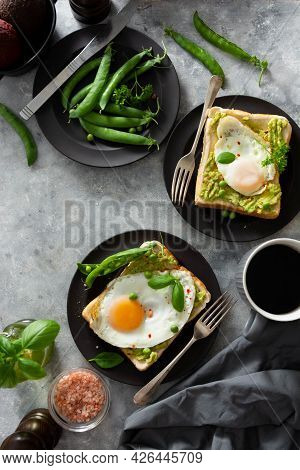 Avocado Toast With Fried Eggs And Fresh Green Peas, Coffee Cups. Dark Background.