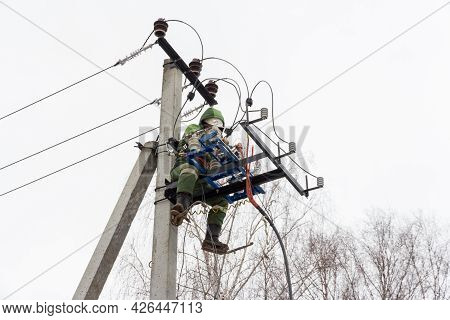 Repair Of Electrical Networks. Power Electrician Lineman At Work On Pole. Electrician Are Climbing O