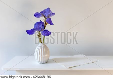 Blue Iris In A Corrugated Vase With A Piece Of Craft Paper On A White Table. Place For Text