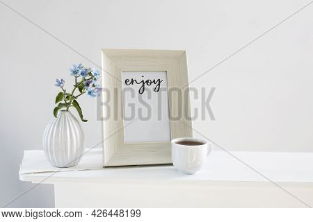 Flower Hackelia Velutina In A White Fluted Vase In The Style Of The Seventies, A Photo Frame With Th