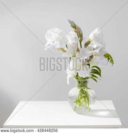A Bouquet Of Three White Irises And A Fern In A Transparent Vase On The Table.