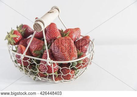 White Metal Basket With Wooden Handle With Fresh Strawberries Is On The White Table. Breakfast