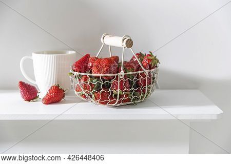 White Metal Basket With Wooden Handle With Fresh Strawberries And Corrugated Ceramic Tea Cup On Beig