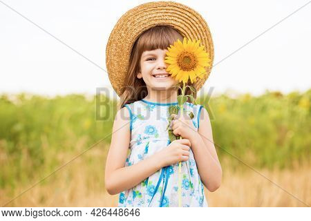Beautiful Little Girl In Straw Hat With Fluttering Hair Smile And Hide Eye With Sunflower Flower, Wa