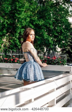 Rear View, Portrait Of A Young Chic Woman In A Blue Festive Short Dress Standing On The Open Veranda