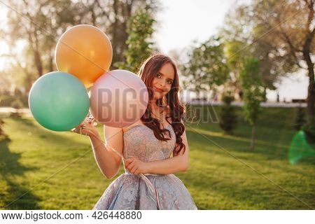 Lifestyle Close-up Portrait Of A Young Woman In A Smart Blue Embroidered Dress With Colorful Balloon