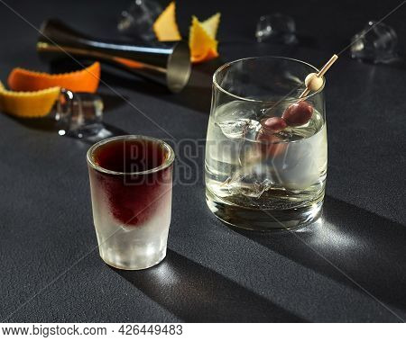 Shot Of Herbal Liqueur And Goblet Of Gin With Ice And Olives