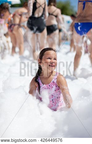 A Happy Laughing Girl In A Pink Swimsuit Plays With Foam At A Foam Party At A Water Park On A Sunny