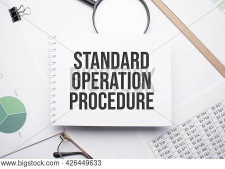 On The Notepad For Writing The Text Standard Operation Procedure, Magnifier,charts And Glasses.