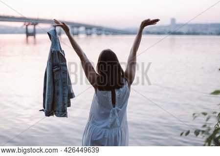 Summer Lifestyle, A Young Woman With Her Back In A White Dress Happily Waving Her Raised Hands And H