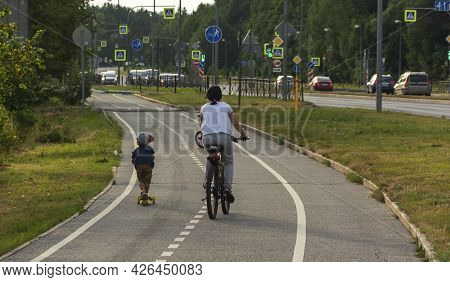 Mom And Child Ride A Bicycle And Scooter On A Bike Path In The City, Family Bike Ride, Active Recrea