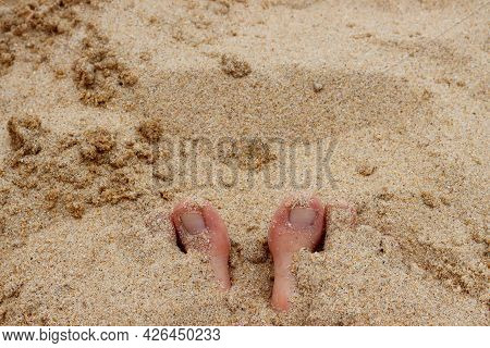 The Feet Are Completely Immersed In The Sand And Two Toes Are Visible.the Big Toes Stick Out Of The