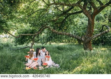 Happy Family Having Summer Picnic Outdoors. Young Parents With Two Pretty Daughters Spending Free Ti
