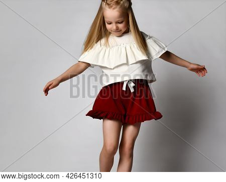 Little Blonde Girl Dances And Whirls On A White Background. Child In A White T-shirt And Red Shorts