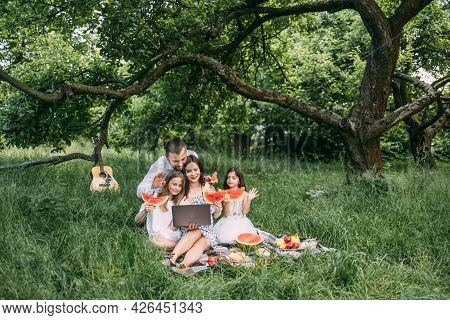 Young Parents With Two Little Daughters Having Video Call On Laptop During Picnic Time At Green Gard
