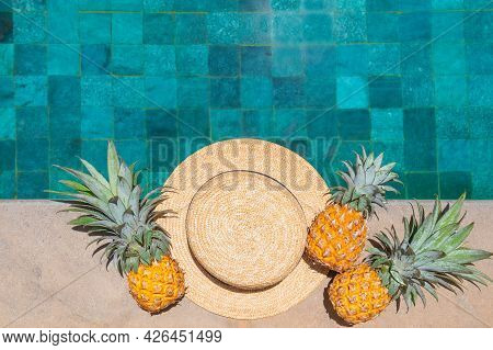 Straw Hat And Three Pineapples By The Refreshing Pool, Viewed From Above.